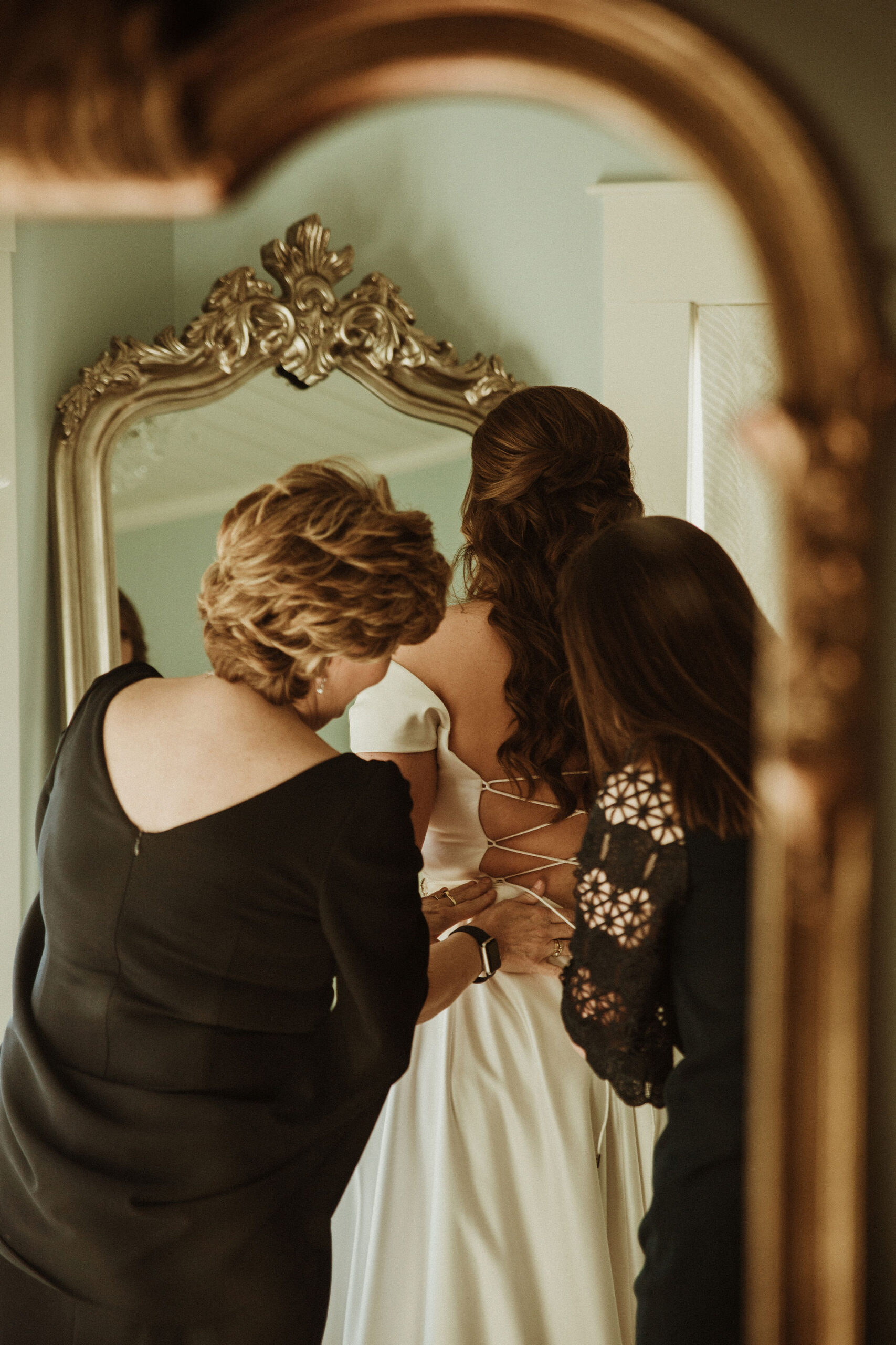 Mother and friend dress bride in bridal changing room
