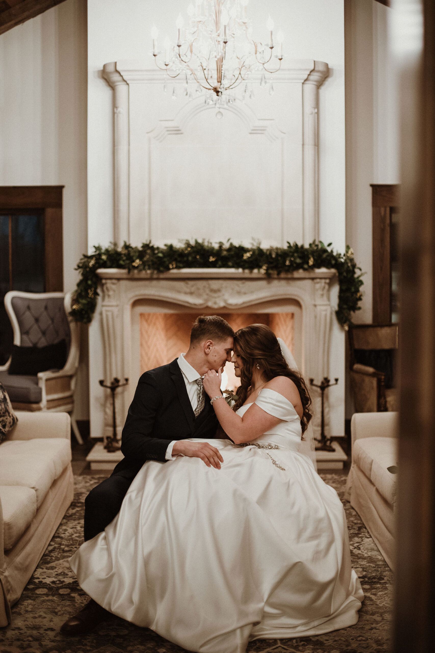 Groom and bride gaze In front of fireplace