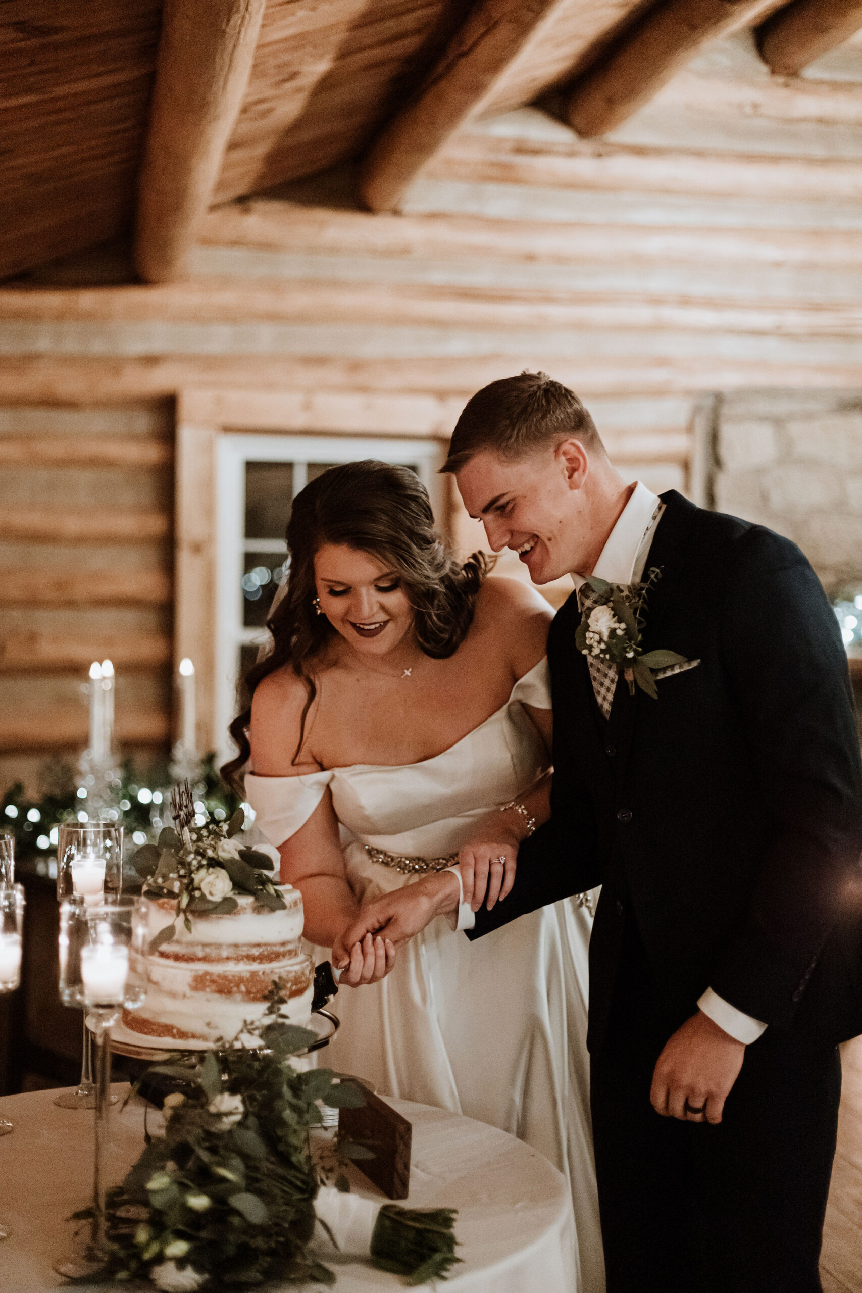 Bride and groom cut cake in cabin